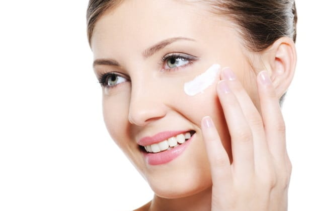 Pretty smiling female applying cosmetic cream on face